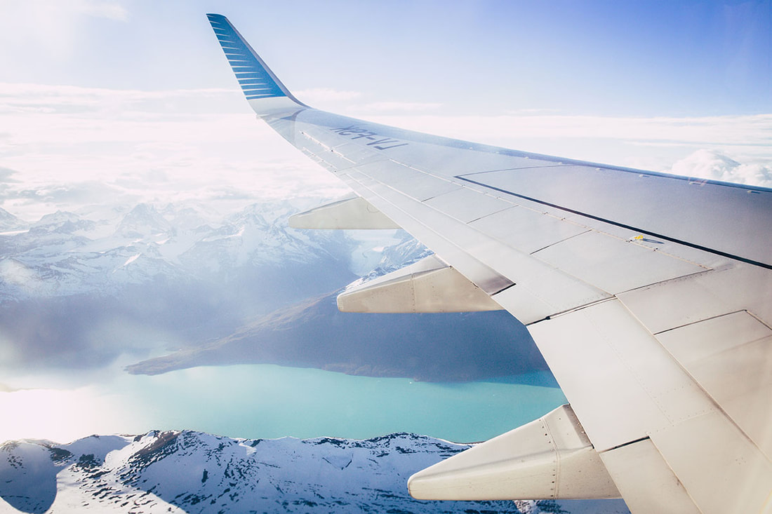 Wing of an airplane and snow-capped mountains