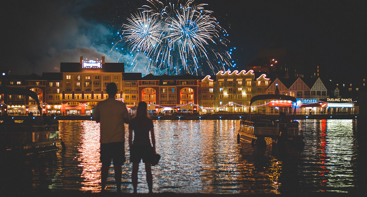 couple taking a celebratory vacation and standing in front of a fireworks display